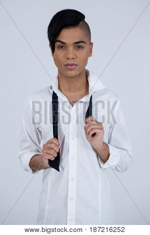 Portrait of confident transgender female holding tie while standing against white background