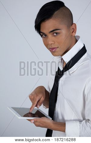 High angle portrait of tansgender woman using digital tablet while standing against white background