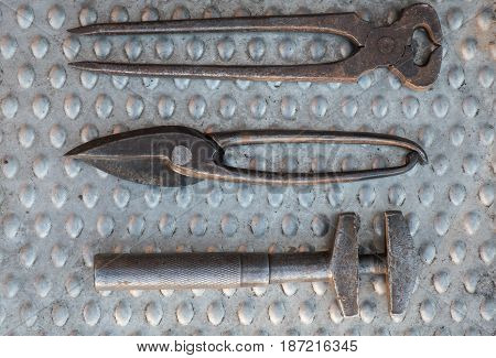 Vintage hand tools on aluminum plate close up, end cutting nippers, adjustable wrench and tin scissors