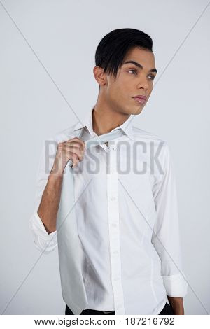 Thoughtful transgender young female standing against white background