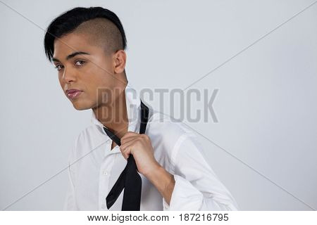 Confident transgender female holding tie while standing against white background