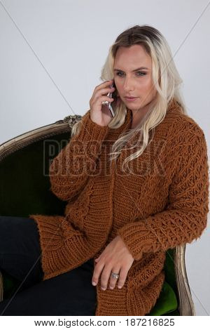 Transgender woman using mobile phone while sitting on chair against gray background