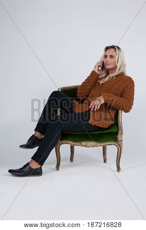 Transgender using mobile phone while sitting on chair against gray background