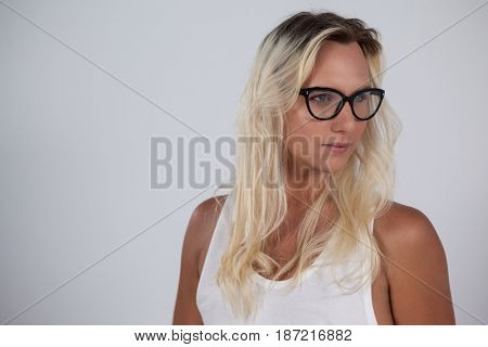 Transgender woman wearing eyeglasses looking away against green background
