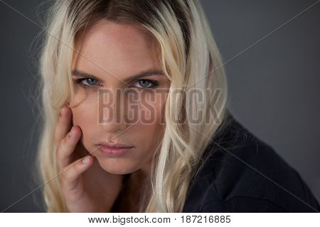 Close up portrait of beautiful transgender woman against gray background