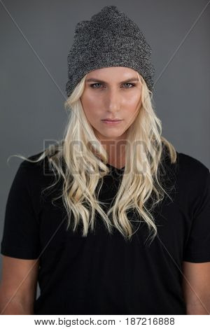 Portrait of beautiful transgender woman wearing knit hat gray background