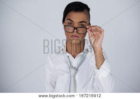 Portrait of transgender woman adjusting eyeglasses while standing over gray background