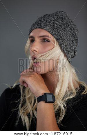 Transgender woman wearing knit hat gray background