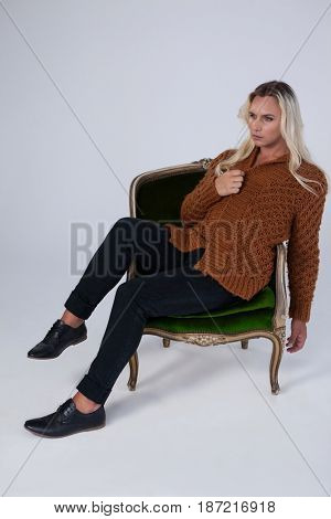 Transgender woman looking away while sitting on chair against gray background