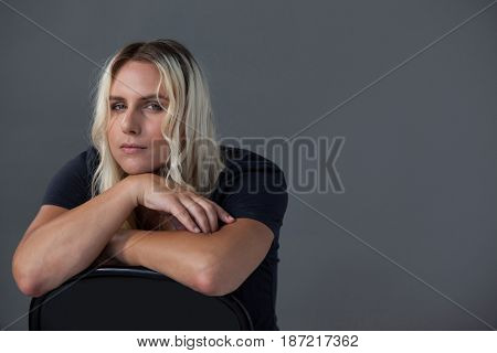 Portrait of beautiful transgender woman leaning on chair against gray background