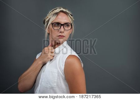 Transgender woman with hairstyle looking away over gray background