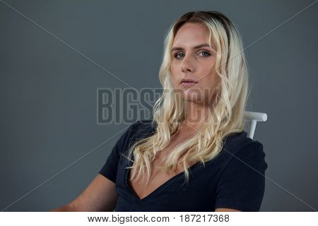 Portrait of beautiful transgender woman sitting on chair against gray background