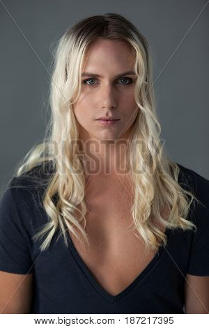 Portrait of transgender woman with long blond hair standing over gray background