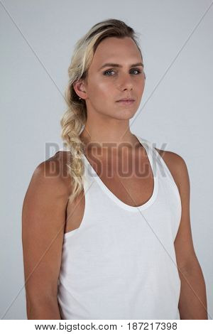 Portrait of beautiful transgender with braided hair standing against gray background