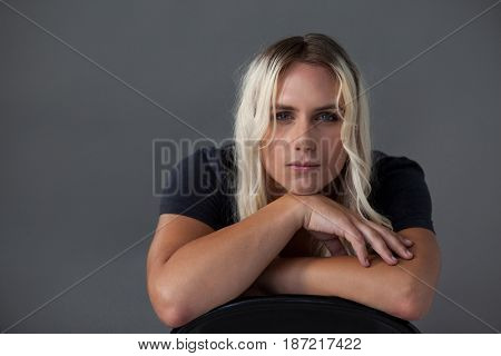 Portrait of beautiful transgender woman leaning on chair over gray background