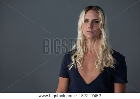 Portrait of transgender woman with blond hair standing over gray background