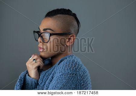 Transgender woman wearing eyeglasses over gray background