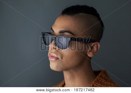 Close up of transgender woman wearing sunglasses looking away against gray background