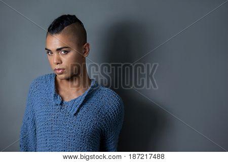 Portrait of confident transgender standing against gray background