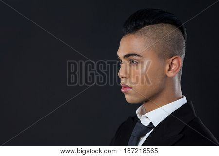 Close up of transgender woman standing over black background