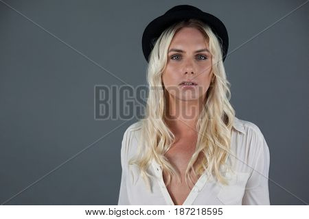Portrait of transgender woman wearing hat while standing over gray background