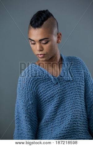 Transgender woman looking down while standing against gray background