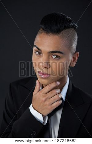 Portrait of transgender woman in full suite against black background