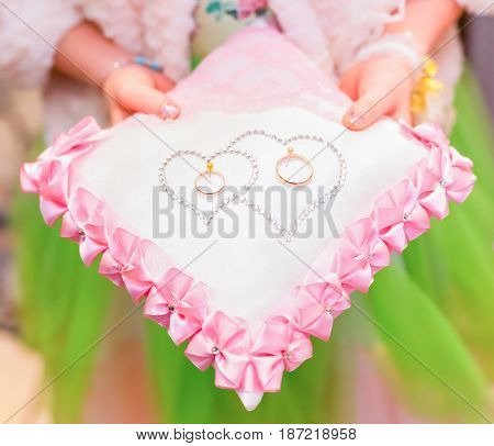Girl Holding Wedding Rings On A Beautiful Pillow