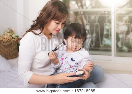 Lovely princess is applying the make up on her skin with special brush as she wants to look like her adult mother
