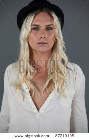 Portrait of transgender woman wearing hat while standing against gray background