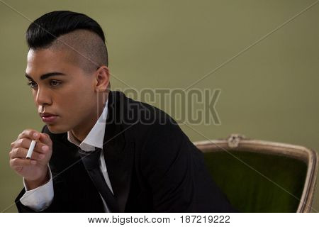 Transgender woman holding cigarette while sitting on chair against green background