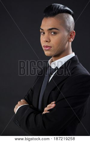 Portrait of transgender with arms crossed against black background