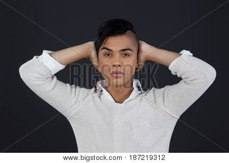 Portrait of transgender woman with arms raised against black background