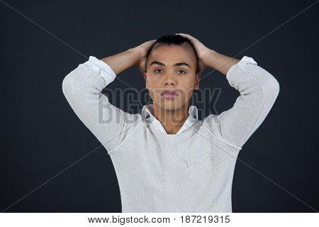 Portrait of transgender woman with hands behind back over black background