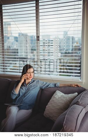 Woman talking on mobile phone while sitting on sofa at home