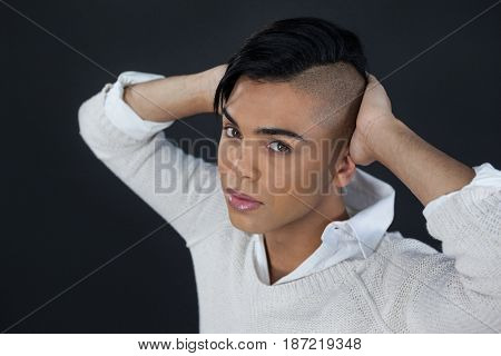 High angle portrait of transgender woman with hands behind back over black background