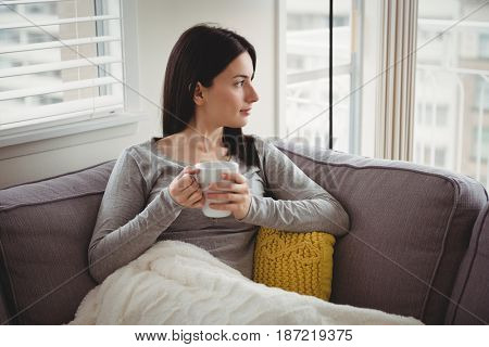 Woman holding cup while looking through window at home