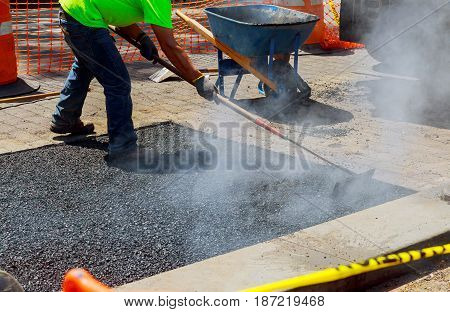 Men at work, urban road under construction, asphalting in progress, workers install sewer manhole