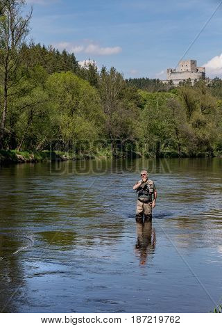 A fisherman with a pole hunts trout. A man in sport fishing tackle flies on a river. In the background on the hill is Rabi Castle. A man flying on the river Otava South Bohemia Czech republic.