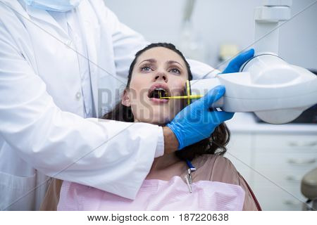 Dentist taking x-ray of patients teeth at dental clinic