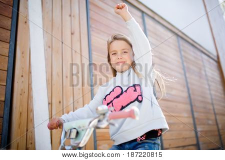 Photo of girl on bicycle near wooden building