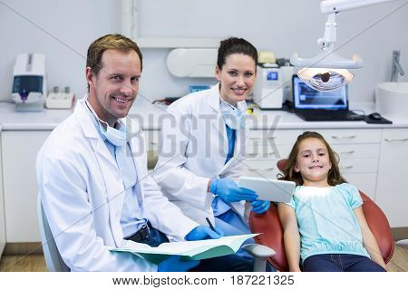 Portrait of smiling dentists and young patient in dental clinic