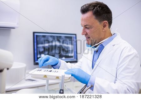 Attentive dentist checking tools in dental clinic