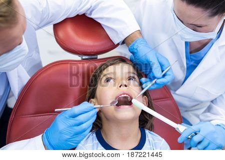 Attentive dentists examining young patient in dental clinic