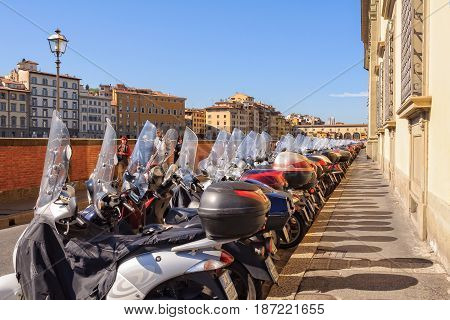 Parking mopeds on Lungarno Generale Diaz an embankment along the Arno river - Florence Tuscany Italy, 11 October 2011