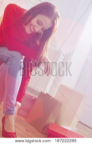 Happy young woman trying on footwear in store