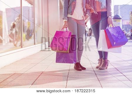 Low section of female friends holding shopping bags on sidewalk