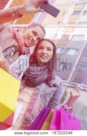 Women with shopping bags taking self portrait through mobile phone