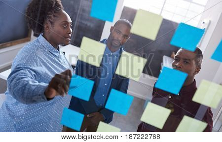 Three casually dressed African work colleagues brainstorming together with sticky notes on a glass wall while standing in a modern office