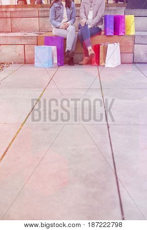 Low section of female friends with shopping bags sitting on steps with sidewalk on foreground